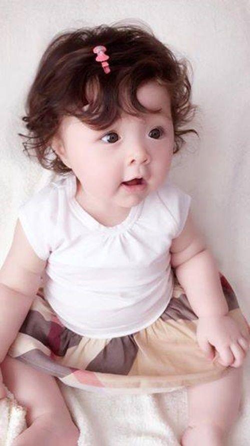 Ảnh em bé dễ thương với mái tóc xoăn và đôi mắt to tròn