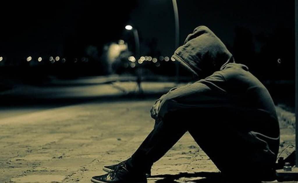 Chàng trai ngồi buồn một mình trên con đường
