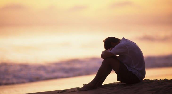 Chàng trai ngồi ôm mặt khóc bên bờ biển
