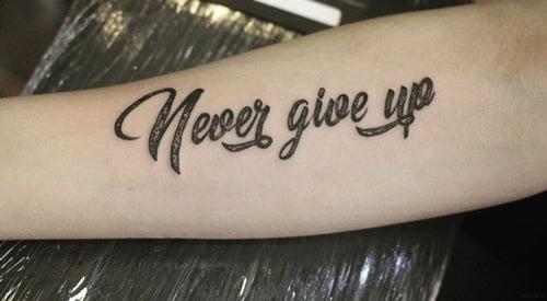Chữ Never Give Up Xăm trên tay
