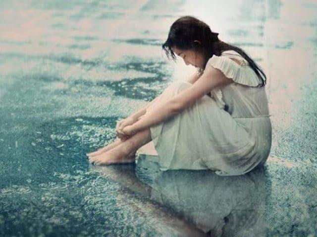 Cô gái ngồi buồn dưới mưa