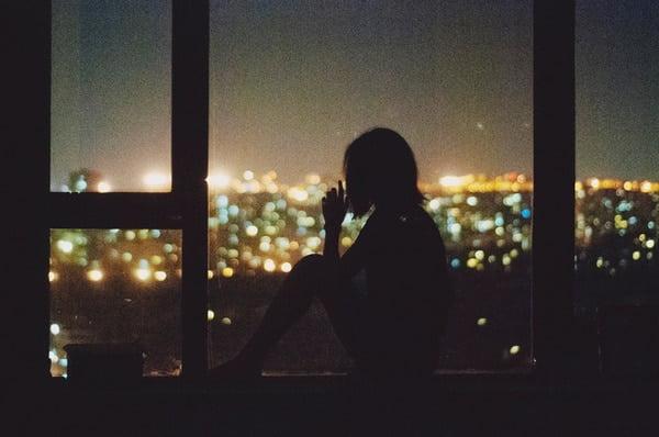 Cô gái ngồi một mình nhìn ra cửa sổ trong đêm tối