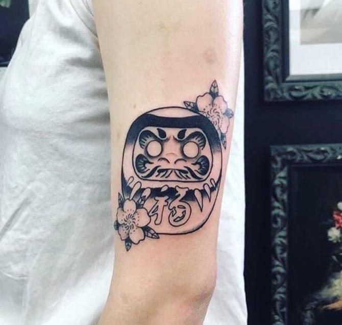 Daruma đen trắng xăm trên cánh tay