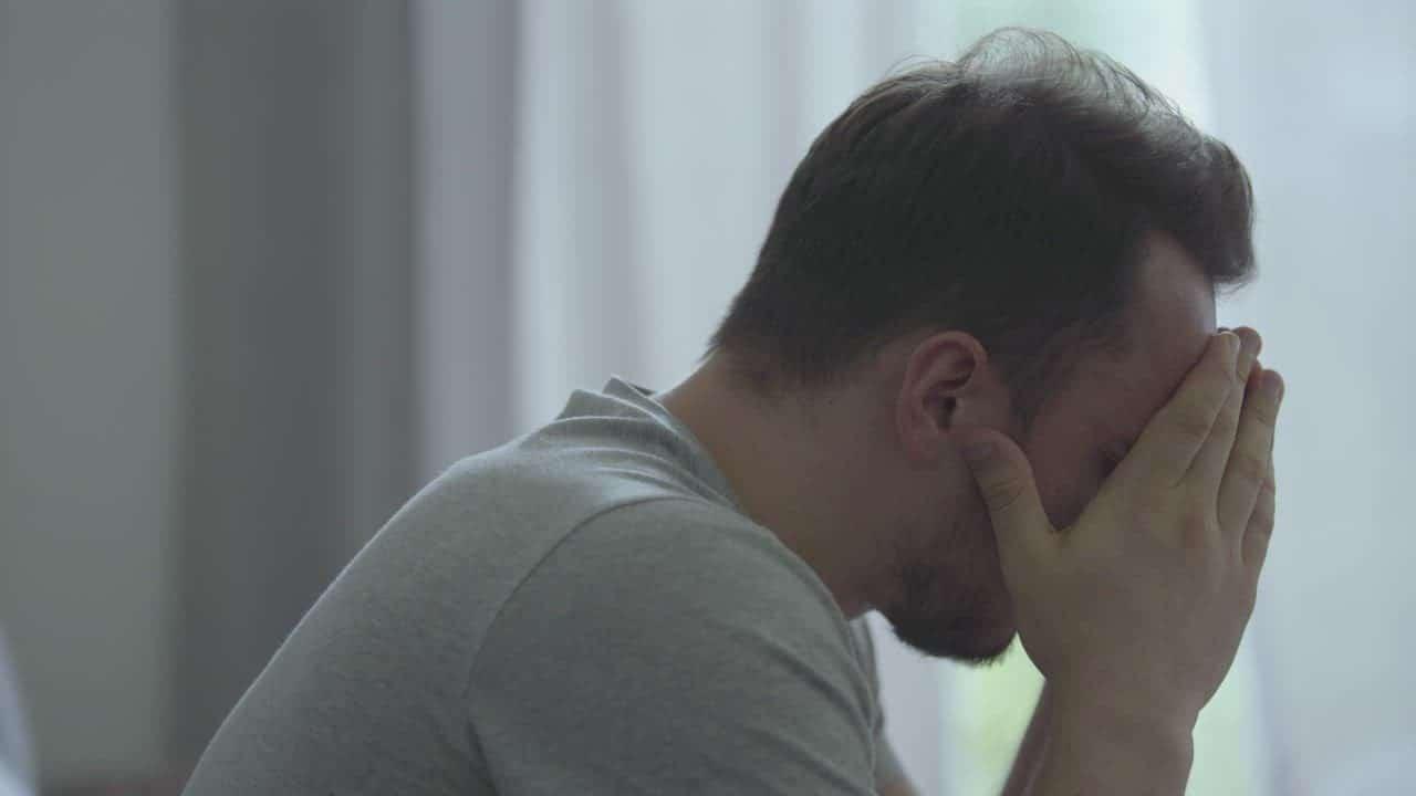 Hình người đàn ông buồn ôm mặt khóc