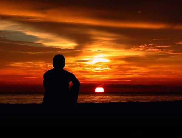 Người con trai ngồi nhìn mặt trời lặng một mình và cô độc