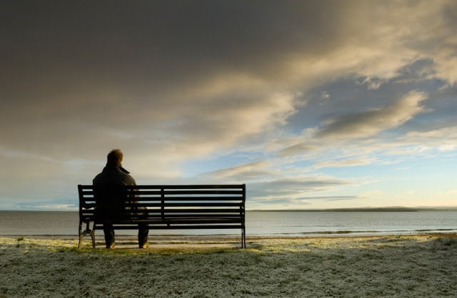 Người đàn ông ngồi nhìn bờ biển một mình cô đơn