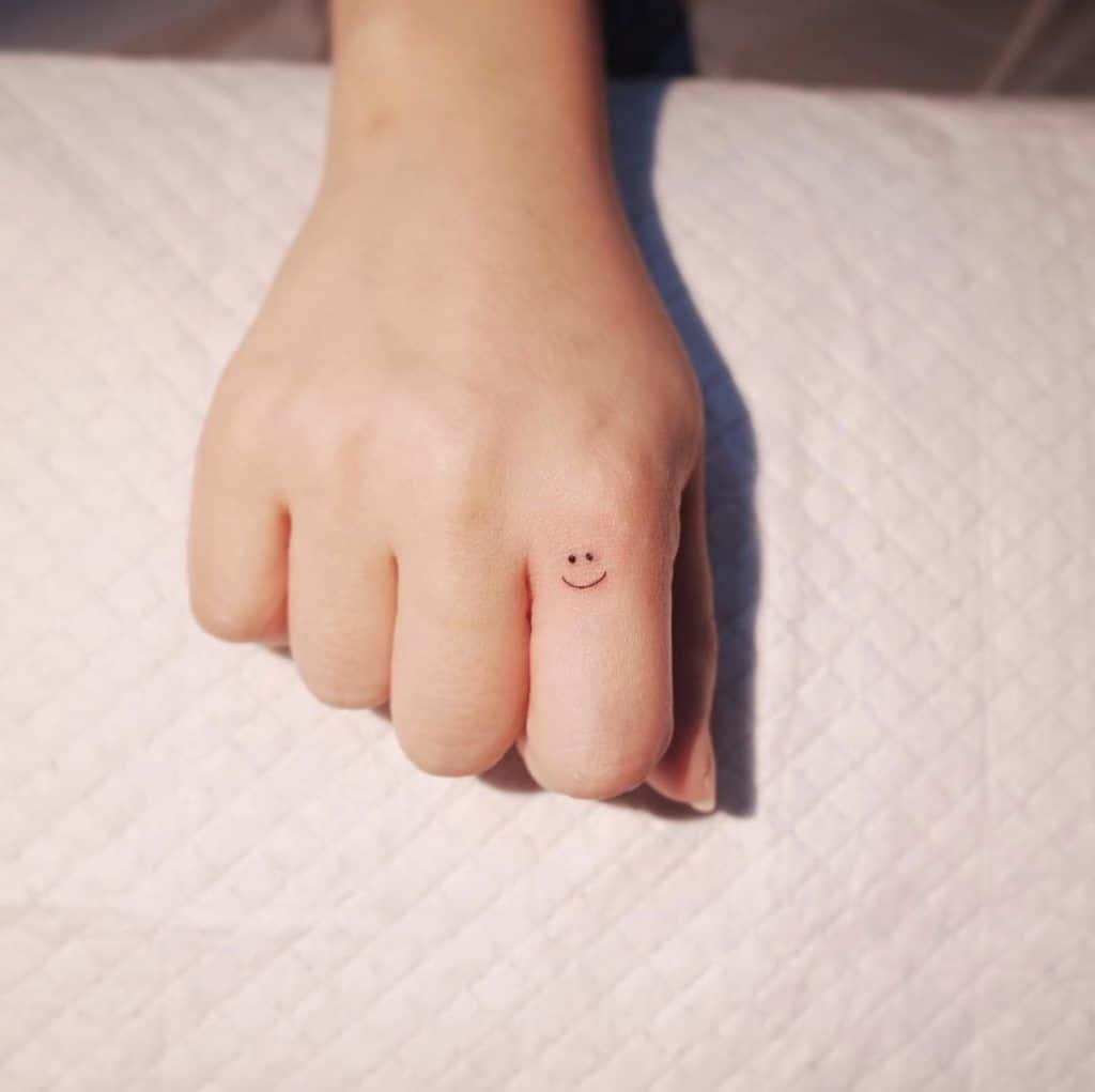Ảnh xăm mặt cười đáng yêu ở ngón tay