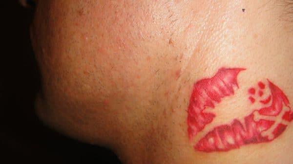 Hình xăm môi hôn và khuôn mặt nhỏ ở cổ